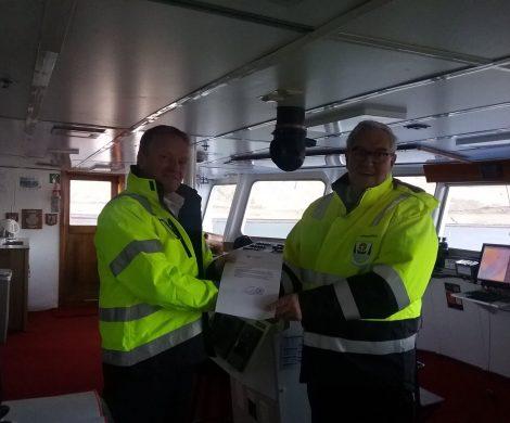 Der Hafenmeister von Isafjördur überreicht dem Kapitän der OCEAN DIAMOND die Genehmigung