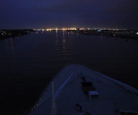 Langsam gleitet die Queen Mary 2 in den hell erleuchteten Hafen, die Stadt schläft noch