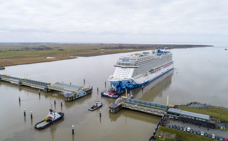 Die Norwegian Bliss hat die Meyer Werft in Papenburg verlassen. Ihre Ankunft in Eemshaven, Niederlande, ist für heute geplant. Ihre Reise auf der Ems in Richtung Nordsee, die sie rückwärts zurücklegen wird, begann nach der Fahrt durch die enge Schleuse der Meyer Werft mit lediglich etwas mehr als einem Meter Spielraum.