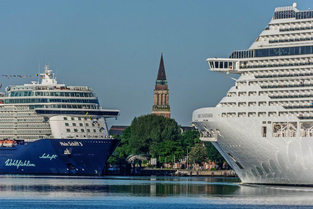 """In Kiel ist es unter dem Motto Kreuzfahrtschiffe (k)entern zu einer ersten Demonstration gegen zu viele Kreuzfahrtschiffe gekommen: Wie die """"Kieler Nachrichten"""" berichten, versammelte sich eine Gruppe mit Protestplakaten vor dem Ostseekai."""